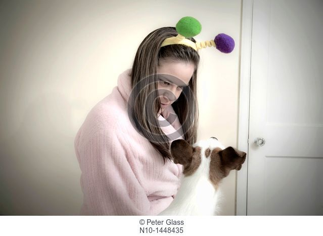 Young woman, wearing pom-poms on her head, with her dog