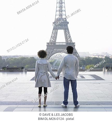 Couple holding hands and looking at Eiffel Tower