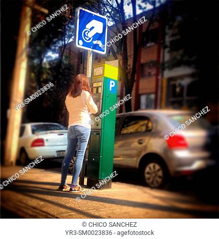 A woman pays in a parking meter in Colonia Roma, Mexico City, Mexico