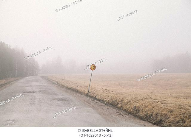 Country road by field in foggy weather against sky