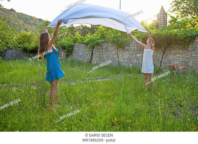 Two Young Women Spreading Blanket In The Garden, Croatia, Dalmatia, Europe
