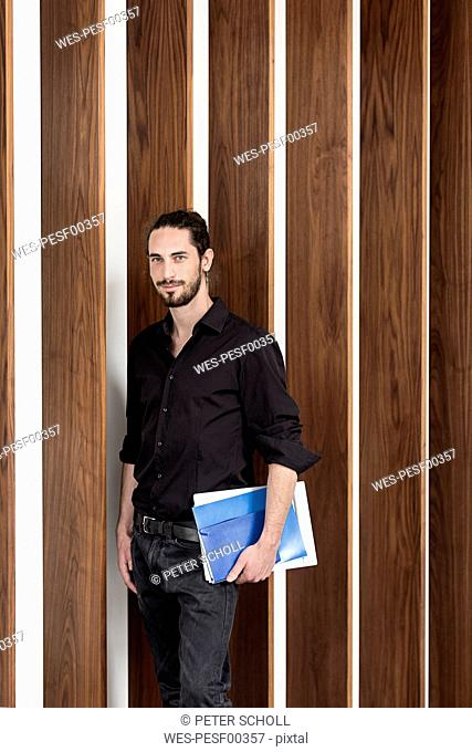 Confident businessman holding folders