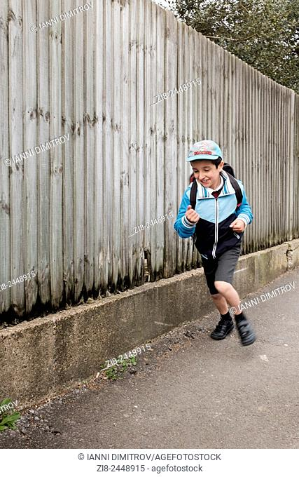 Primary schoolboy,running home after school,Surrey,Uk