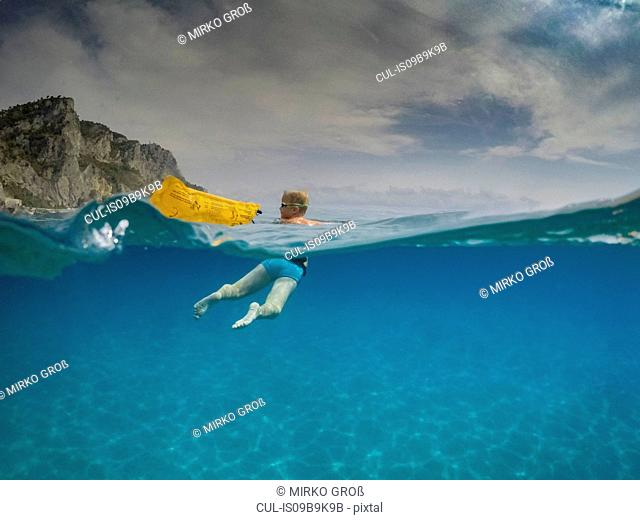 Over underwater view of boy looking back while swimming in blue sea, Varigotti, Liguria, Italy