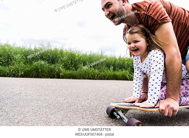 Daughter with father on skateboard