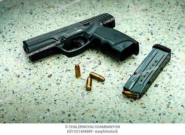Gun with magazine and ammo on floor