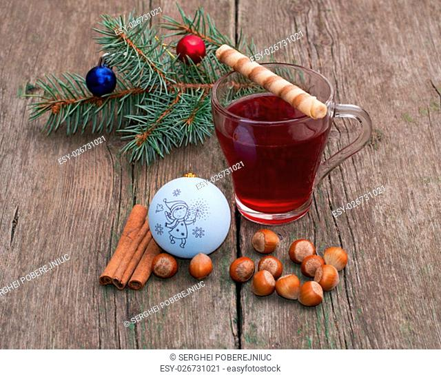 coniferous branch, tea, cinnamon and nutlets, still life subject Christmas and New Year