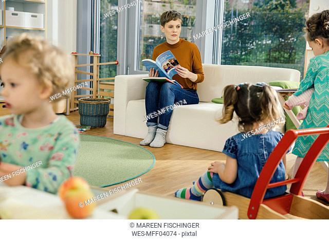 Pre-school teacher with book looking at children in kindergarten