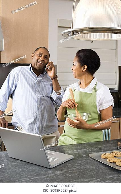 Couple in kitchen with laptop and cellphone