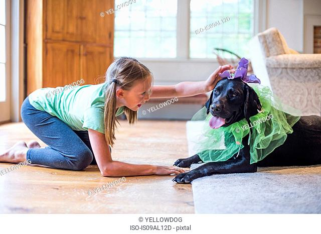 Young girl playing dress up with pet dog