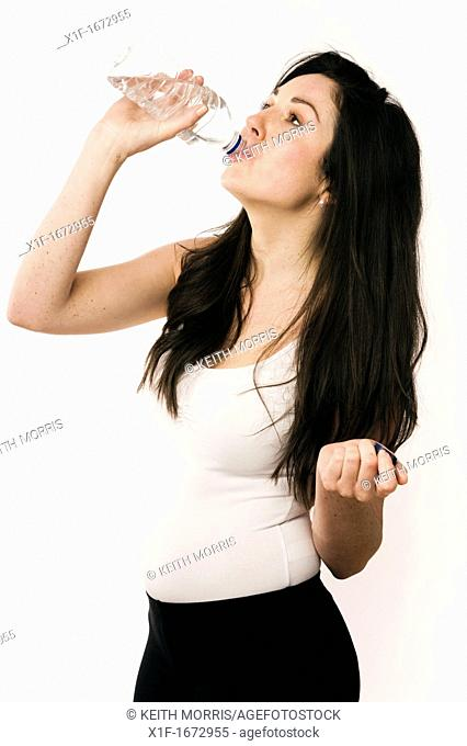 A young woman with brown hair and eyes drinking from a plastic bottle of water
