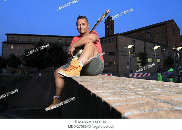 Italian singer and television presenter Paolo Belli posing sitting on a wall before a concert. Città della Pieve, July 2013