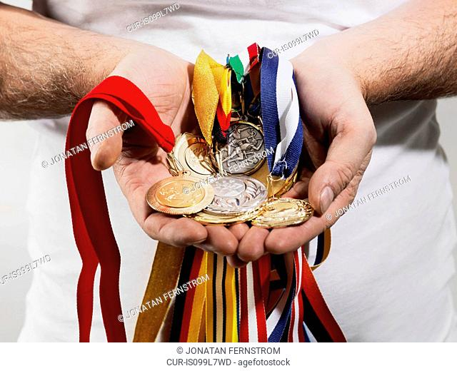 Mature man holding gold medals against white background