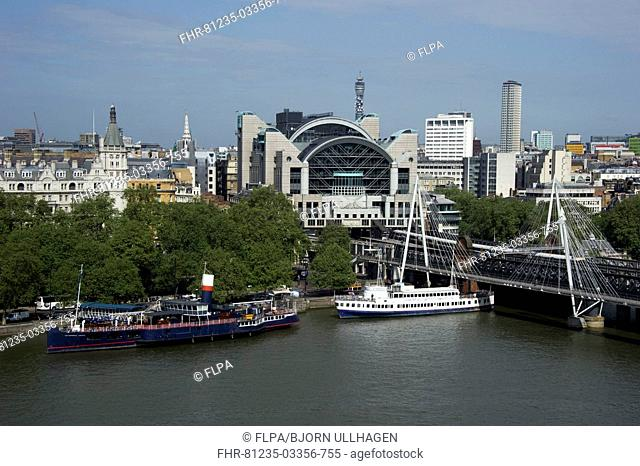 View from London Eye of city river with boats and Charing Cross railway station, Hungerford Bridge, River Thames, City of Westminster, London, England, april