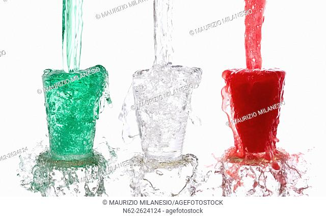 Tricolor drinks poured vigorously into three overflowing glasses on white background