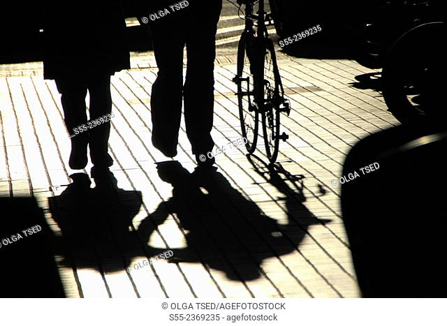 Pedestrians strolling with a bicycle and their shadows. Barcelona, Catalonia, Spain