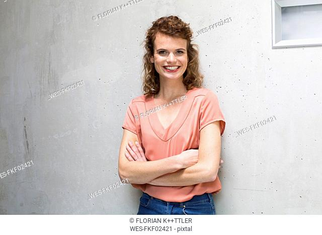 Portrait of smiling woman leaning against concrete wall