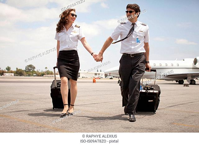 Male and female private jet pilots holding hands at airport