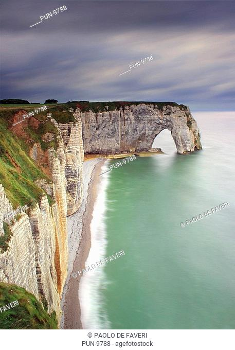 A moody representation, with an incoming storm in the background, of the cliff known as La Manneporte, which is part of the amazing rocky coast around Etretat...