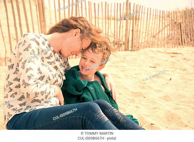 Young woman sitting on beach with son wrapped in blanket
