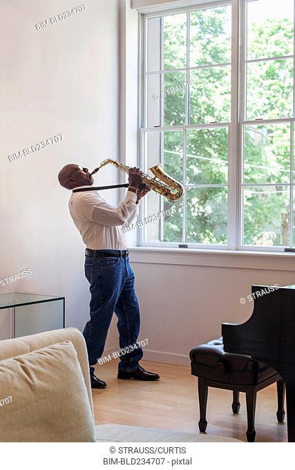 Man playing saxophone near window