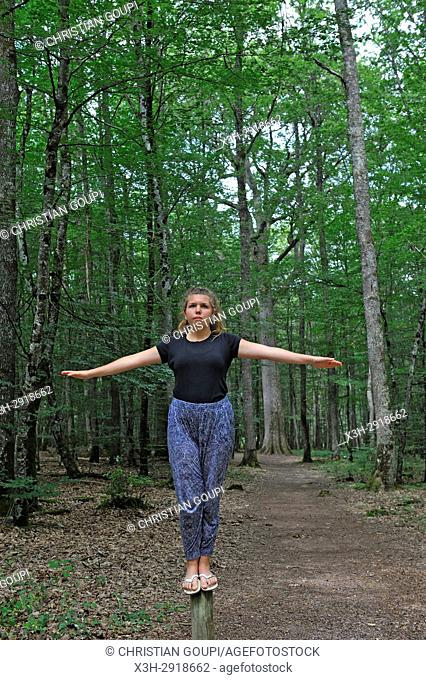 young girl balancing in the Forest of Troncais (Forêt de Tronçais), Allier department, Auvergne-Rhone-Alpes region, France, Europe
