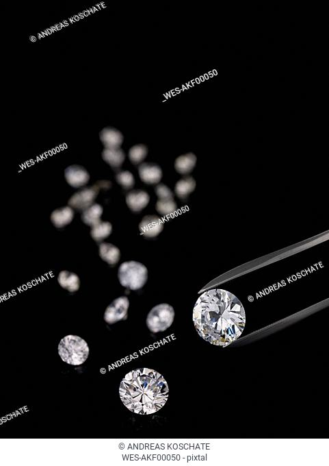 Tweezers and cut diamonds against black background