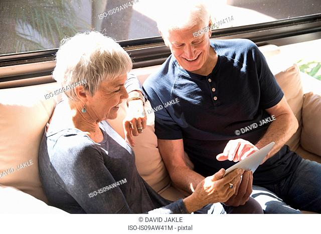 Senior couple, relaxing on sofa, looking at digital tablet