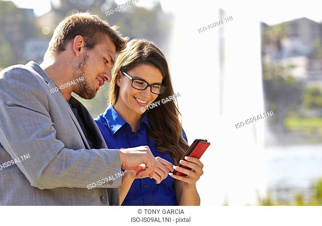 Businessman and woman using smartphone