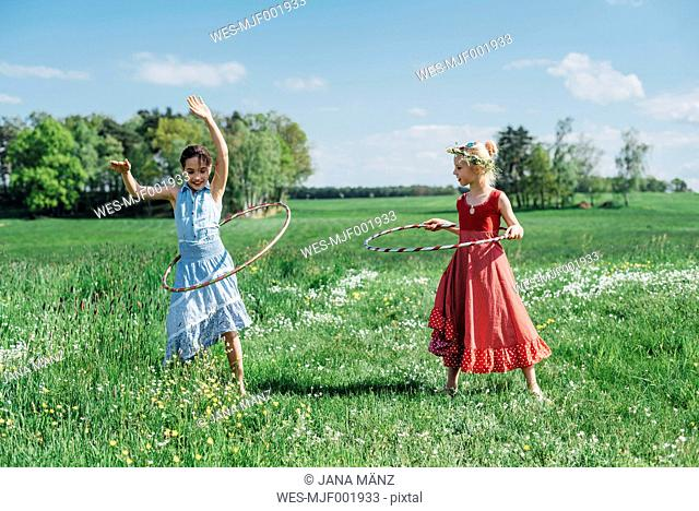Two girls with hula hoops in meadow