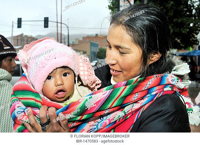 Young mother with baby in a baby-sling, Bolivian Altiplano highlands, Departamento Oruro, Bolivia, South America