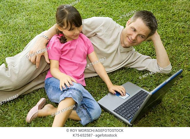 Dad and daughter using laptop outdoors