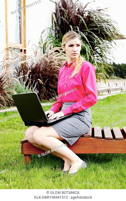 Businesswoman working on a laptop in the backyard