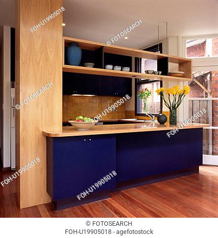 Modern kitchen with wooden shelving above blue fitted unit