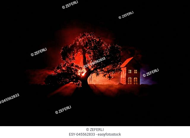 Old house with a Ghost in the forest at night or Abandoned Haunted Horror House in fog. Old mystic building in dead tree forest