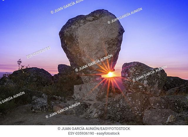 Sun rising between megalithic monument of Cancho Que Se Menea. In English shifting rock. Montanchez, Spain
