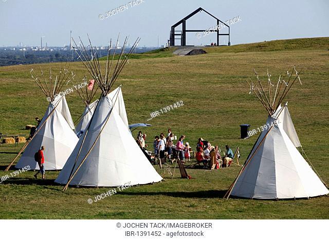Indian tents and art object Hallenhaus on the Halde Norddeutschland mining waste tip near Neukirchen-Vluyn, North Rhine-Westphalia, Germany, Europe
