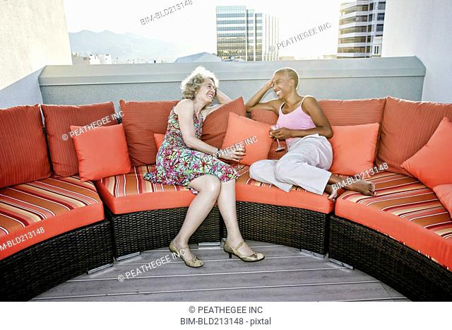 Women drinking wine together on urban rooftop