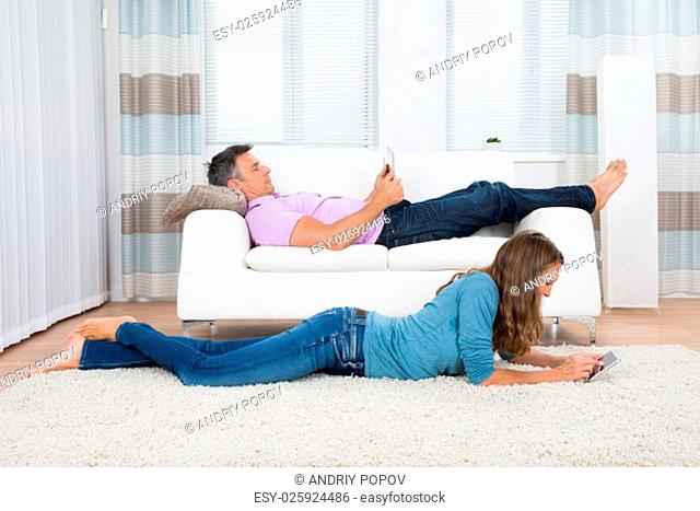 Mature Man And Woman With Digital Tablets Lying On Sofa And Carpet In Living Room