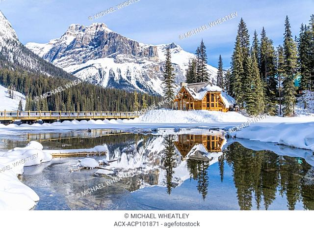 Restaurant of Emerald Lake Lodge complex, reflected in outlet stream at Emerald Lake, Winter, Yoho National Park, British Columbia, Canada