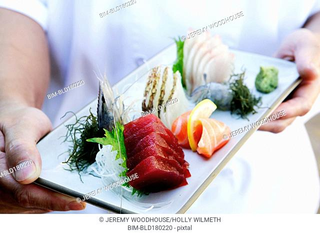 Hands holding tray of fresh sushi