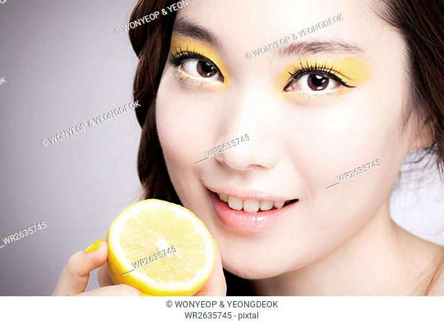 Face of young smiling Korean woman in yellow eye shadow posing with lemon