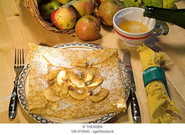 speciality delicacy from Brittany plate with a crepe with apple pieces and a cup of cidre cider in the background bio organic apples in a basket cornucopia