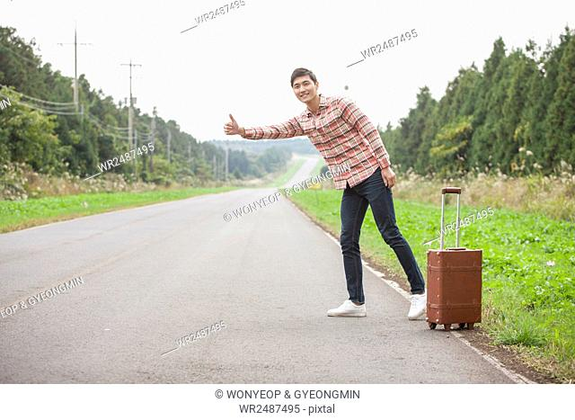 Young man standing and trying to hitch a ride with his carrier on a road