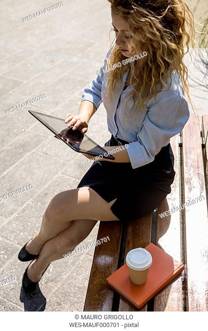 Businesswoman sitting on bench using digital tablet