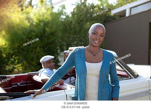 Older woman leaning on convertible