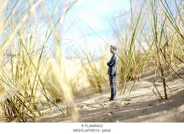 Businessman figurine standing on sand dune, looking at distance