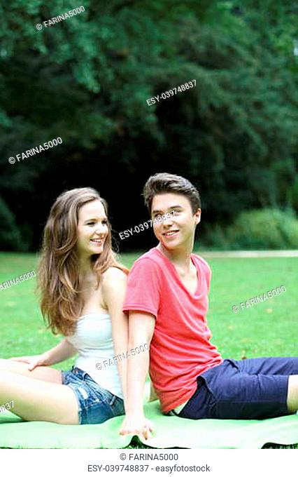 Young teenage couple in the park sitting back to back on the grass looking over their shoulders at each other in a lush green park