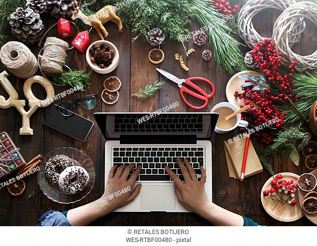 Woman working with laptop at her desk covered with utensils for creating Advent wreaths, partial view