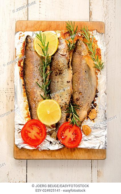 baked trout with lemon, garlic, rosemary, pepper, salt and sliced tomato